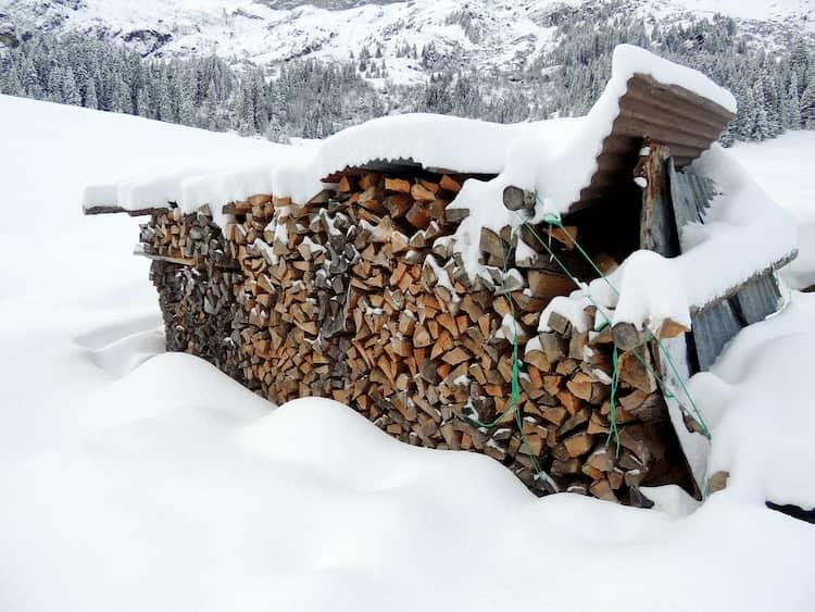 Hier sehen Sie einen abgedeckten Brennholzstapel der von Schnee bedeckt ist.
