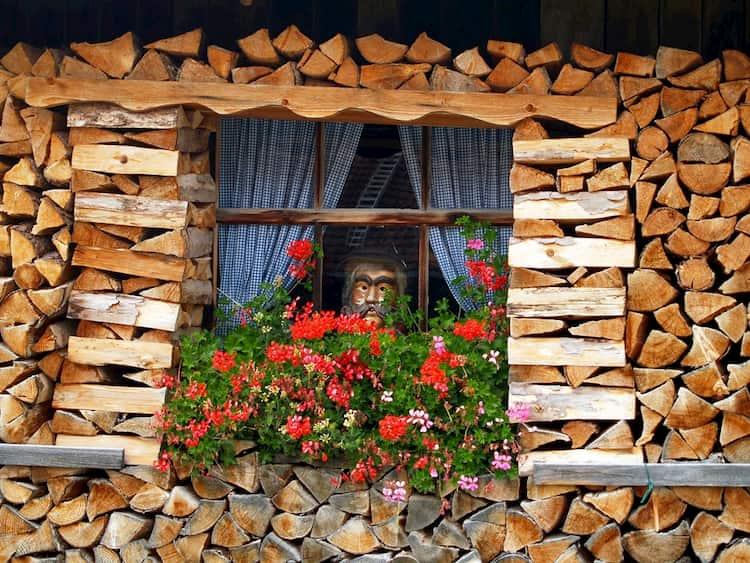 Hier sehen Sie ein Fenster, um welches ein dekorativer Holzstapel gebaut wurde.